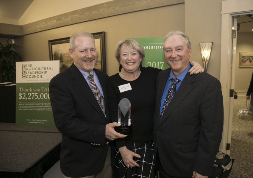 Photo of Mark Haynes, Linda Ford and Mike Haynes holding Hero award.